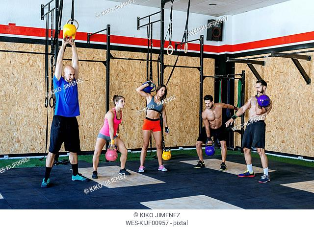 Group of athletes lifting kettlebells in gym