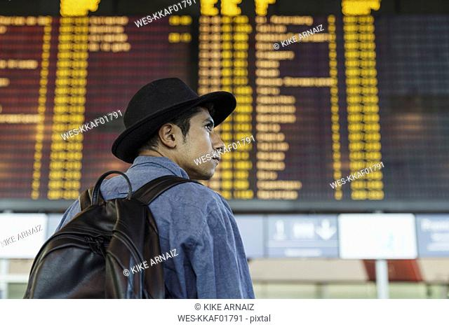 Young man with hat and backpack at arrival departure board at the airport