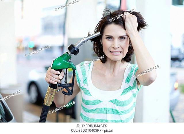 Frustrated woman pumping gas into hair