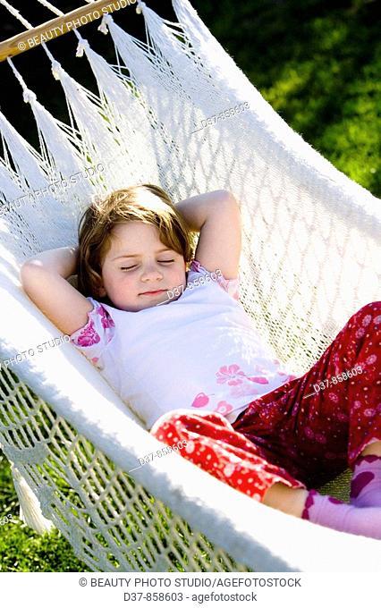 Little girl sleeping on a hammock