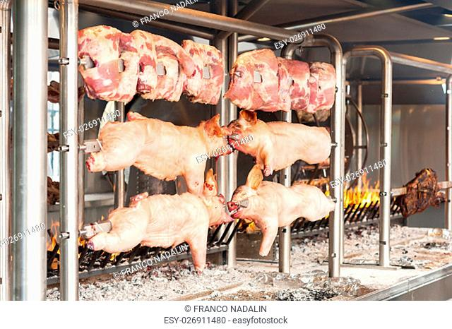 Carcasses of pork and other meat prepared on skewer. Cooking on grill and fire