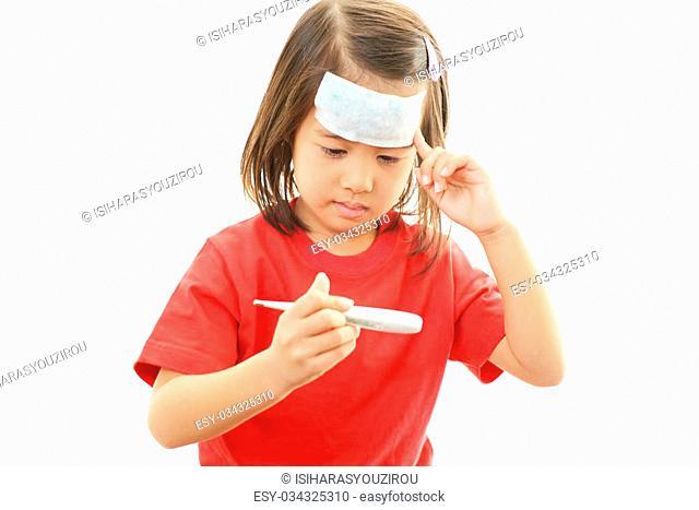 Little girl having flue taking thermometer
