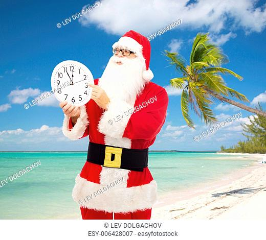 christmas, holidays and people concept - man in costume of santa claus with clock showing twelve pointing finger over tropical beach background