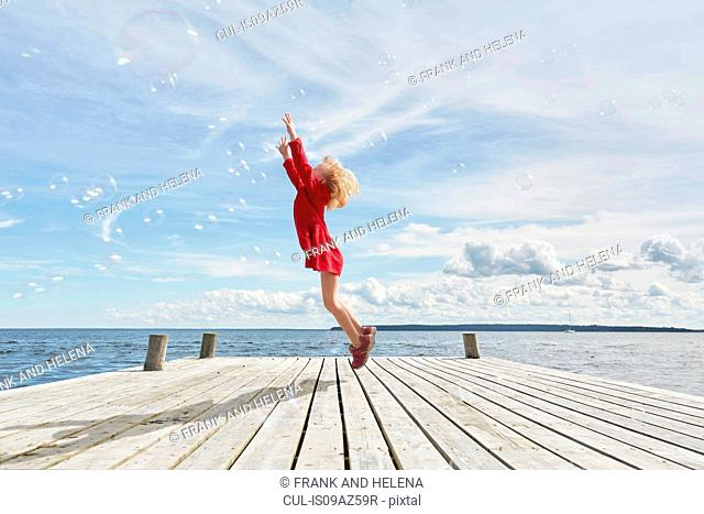 Young girl on wooden pier, jumping to reach bubbles