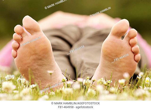 Close-up of undersides of bare feet of woman lying on grass