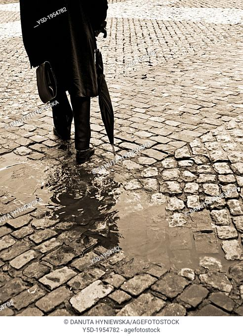 lonely man in long coat walking with umbrella and briefcase, sidewalk, paving stones, after rain, sepia, old fashioned, actually Madrid, Spain, Europeans