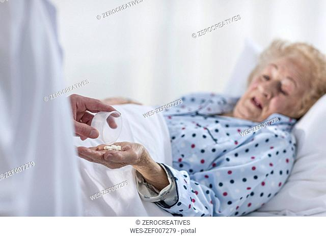 Patient lying in hospital bed receiving medication