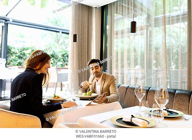 Man and woman sharing a tablet in a restaurant