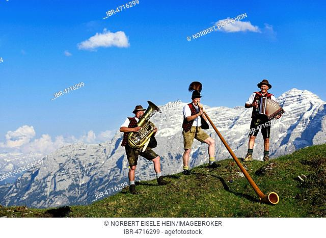 Three folk musicians play in front of mountain panorama, Bergfexn trio in traditional costume on the Eggenalm, behind Loferer Steinberge, Reit im Winkl, Bavaria