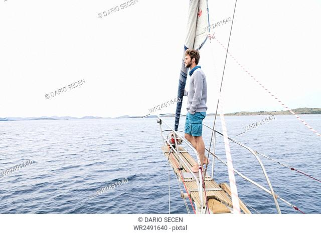 Young man stands on bow of yacht day dreaming