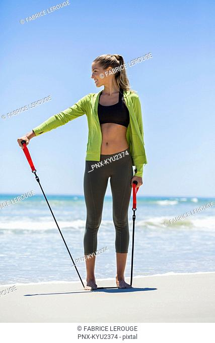 Smiling woman exercising with a resistance band on the beach