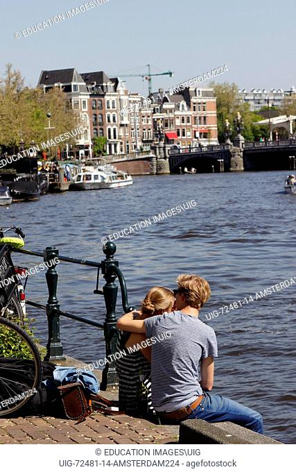 Amsterdam Netherlands Holland Europe young couple sitting canal side on the Amstel canal