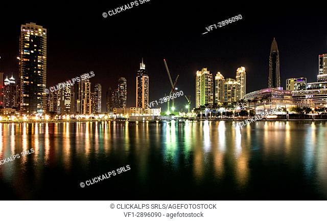 The night skyline show the sequence of bright skyscrapers which are reflected on the water of Burj Khalifa lake. Dubai, United Arab Emirates