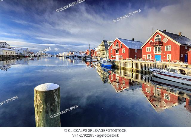 Red houses reflected in the canal of Henningsvaer. Lofoten Islands. Norway. Europe