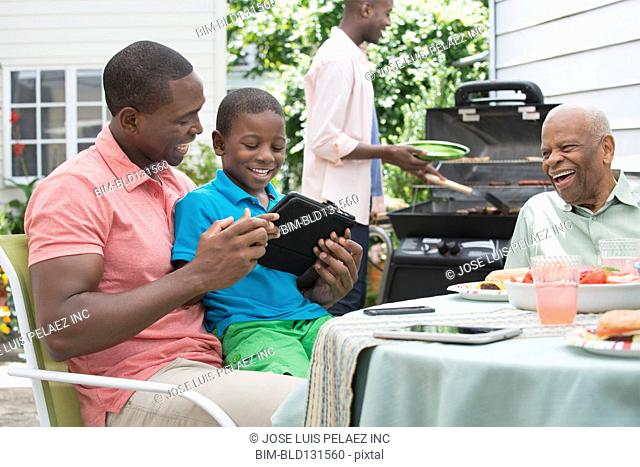 Father and son using digital tablet at barbecue