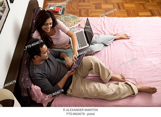 Singapore, Young couple relaxing with laptop and tablet pc in bedroom