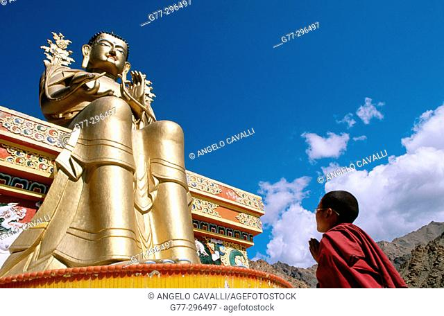 Novice monk praying in front of a giant buddha at Likir Monastery. Ladakh. Jammu and Kashmir, India