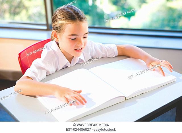 Schoolkid reading braille book in classroom