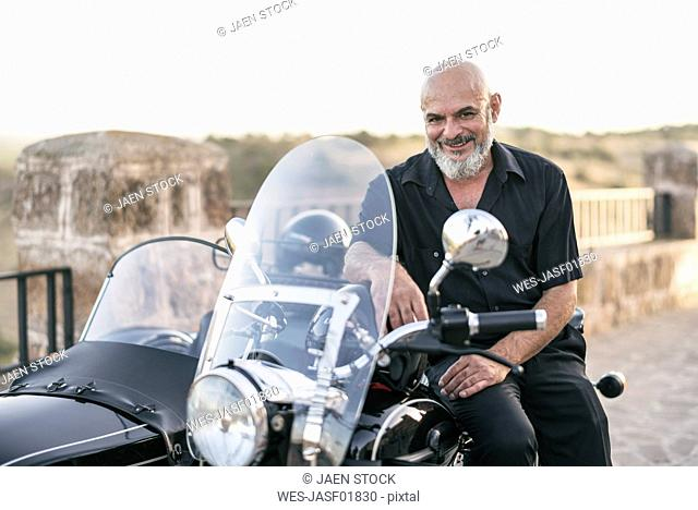 Spain, Jaen, smiling mature man posing on his motorcycle with a sidecar