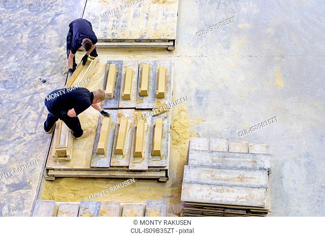 Overhead view of workers moulding stone in architectural stone factory