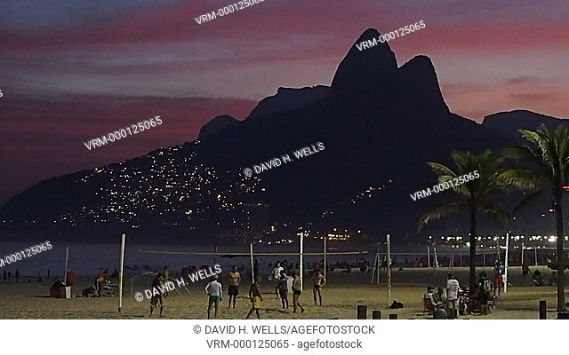 Tourist at beach during sunset, with Dois Irmaos Mountains in background, Ipanema, Rio De Janeiro, Brazil