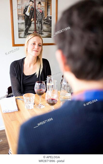 Woman looking at male friend while sitting in restaurant