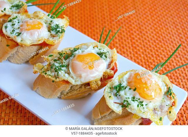 Spanish tapa: fried quail eggs with tomato sauce. Close view