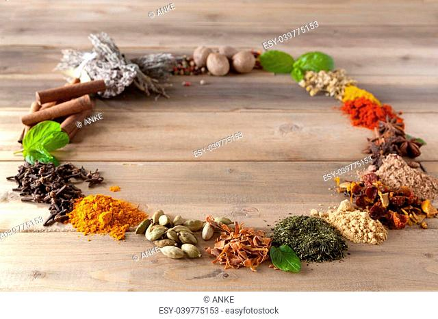 Colorful circle of spices and herbs on a wooden table