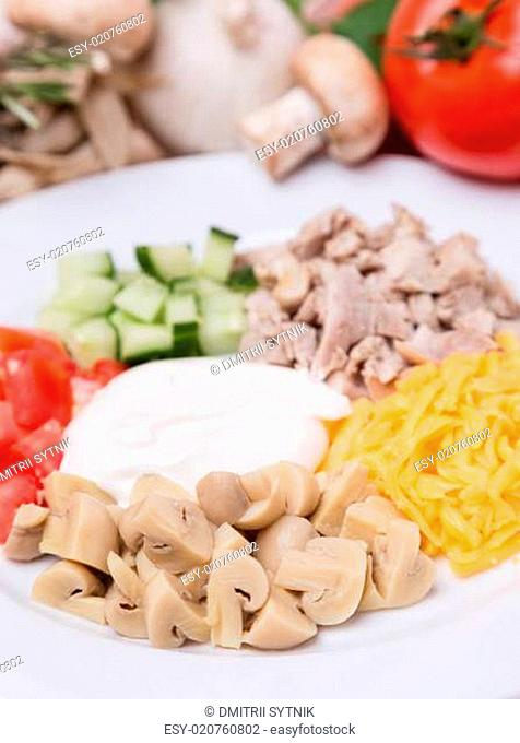 salad from sliced vegetables, meat and champignon with garnish on plate