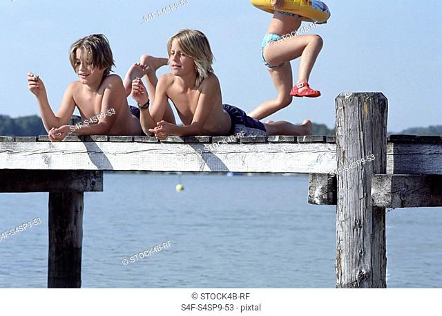 Two Boys lying procumbently on a Footbridge throwing Breadcrumbs into the Water - Friendship - Swimming - Summer - Youth