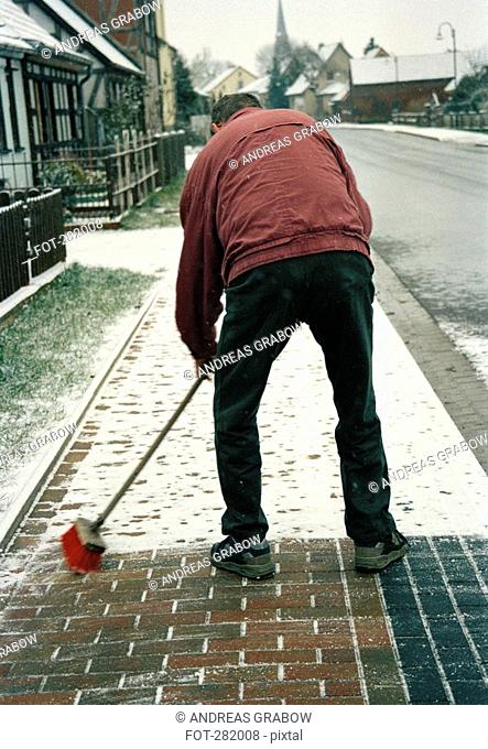 Man sweeping snow on sidewalk