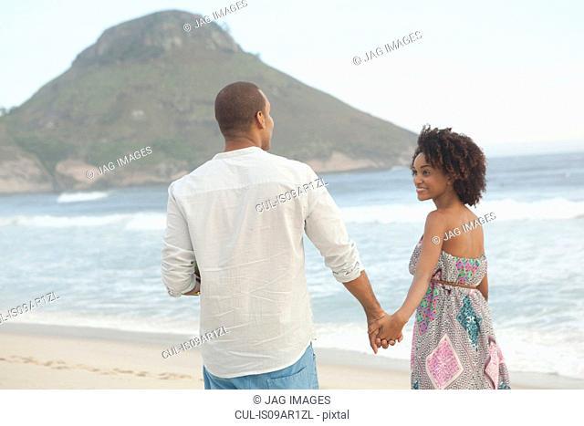Couple strolling hand in hand on beach, Rio De Janeiro, Brazil