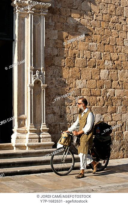 Cyclist in front of Franciscan Monastery south door ,Main boulevard Stadrun, Old Town, Dubrovnik  Croatia