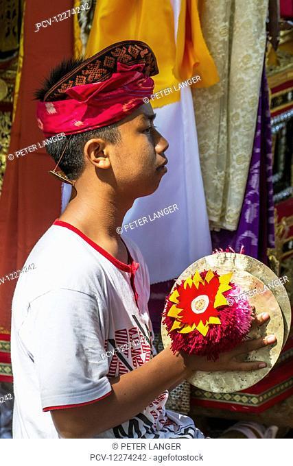 Boy in a gamelan ensemble preforming during a Ngaben or Cremation Ceremony, Klungkung, Bali, Indonesia
