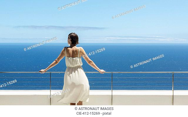 Woman looking at ocean from balcony