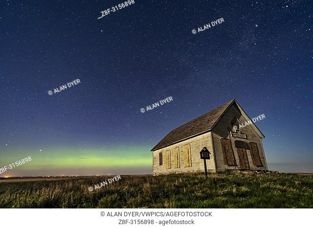 The 1910 Liberty Schoolhouse, a pioneer one-room school, on the Alberta prairie near Majorville, in the moonlight with an aurora across the north