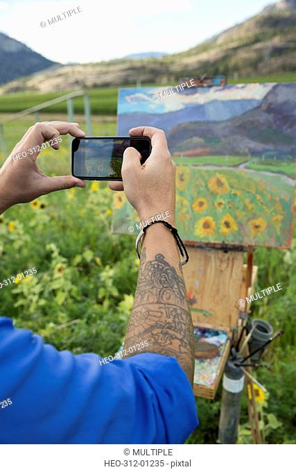 Male painter photographing sunflower painting with camera phone in rural field