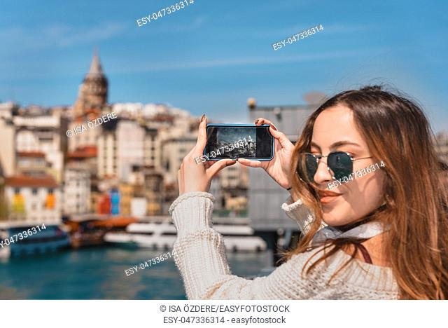 Portrait of beautiful attractive young girl with headphones,smartphone and sunglasses takes selfie on Galata Bridge with view of Suleymaniye Mosque in Istanbul