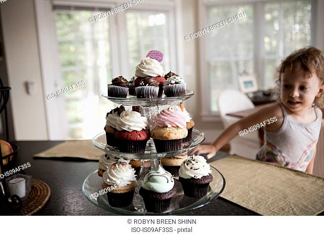 Female toddler looking at cake stand full of cupcakes