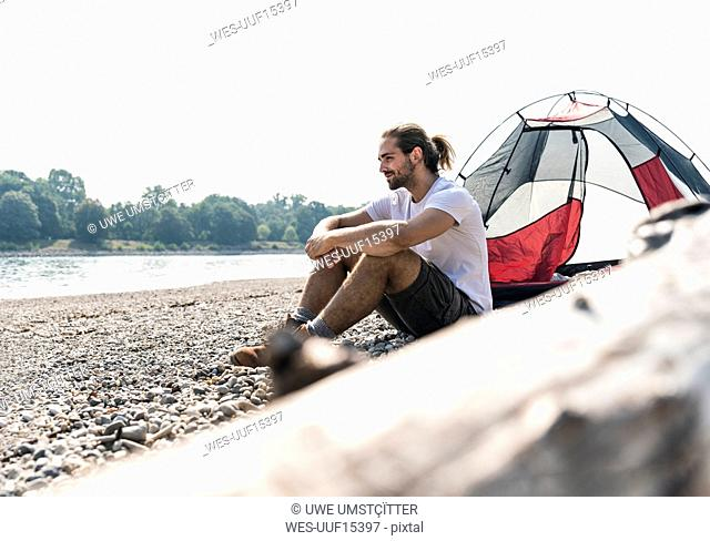 Young man sitting at a tent at the riverside