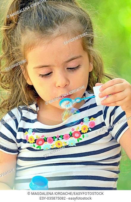 Child blowing soap bubbles in nature