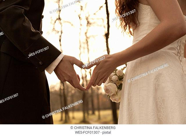 Newly wed bridal couple touching hands, making heart shaped finger frame