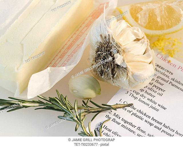 Close-up of butter, garlic, lemon, rosemary and recipe
