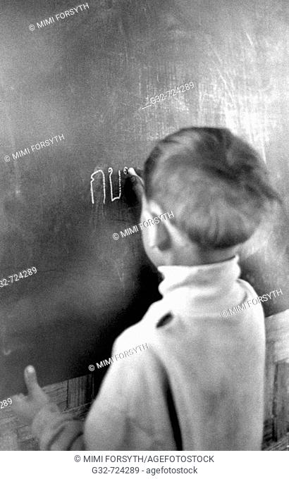 Thai schoolboy writes on chalkboard