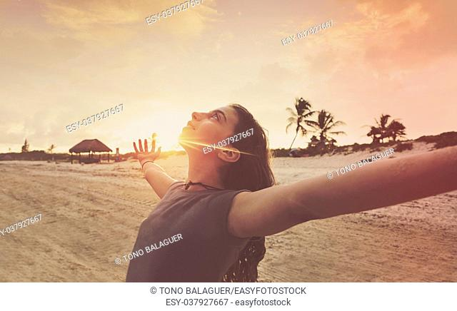 Open arms girl at sunset caribbean beach in Mexico