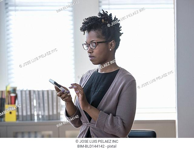 Black businesswoman using cell phone in office