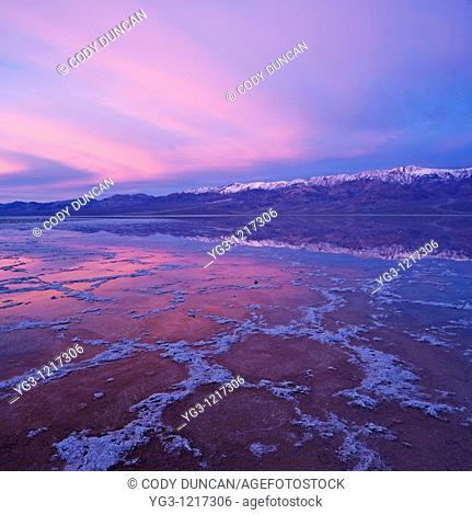 Sunrise reflection in Badwater Basin and Panamint mountains, Death Valley national park, California