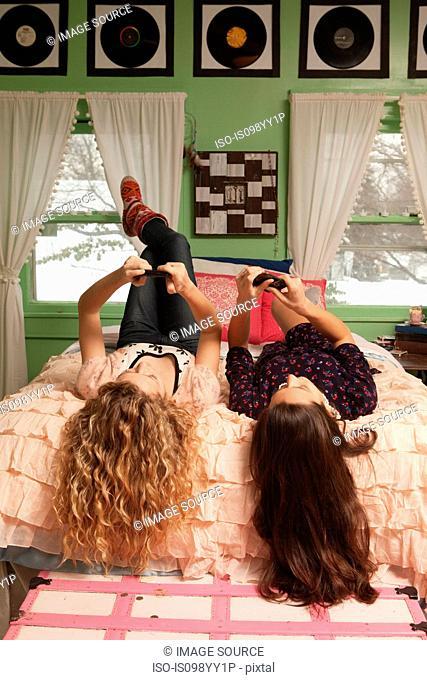 Teenage girls lying on bed with smartphones