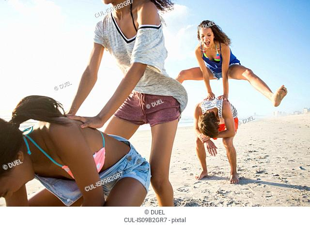 Young man and three female friends playing leapfrog on beach, Cape Town, South Africa
