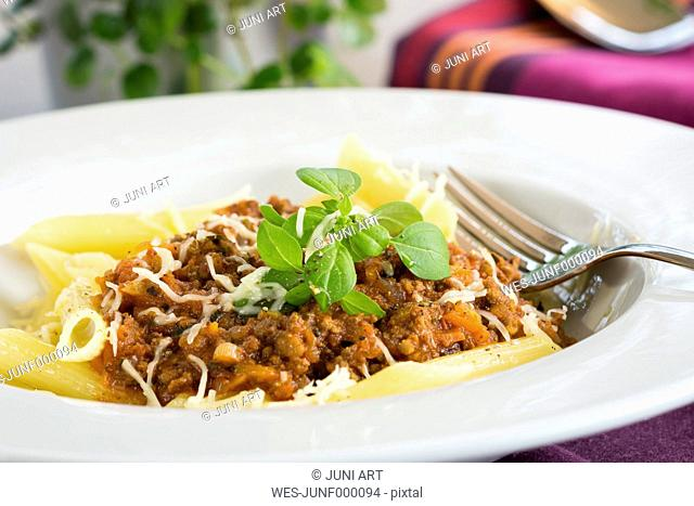 Dish of penne with homemade Bolognese, parmesan and basil